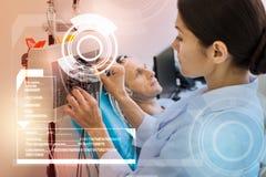 Kalme verpleegster wat betreft de draden terwijl het voorbereiden van alles voor het EEG royalty-vrije stock fotografie
