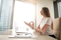 Kalme vreedzame onderneemster het praktizeren yoga op het werk, het mediteren stock foto's