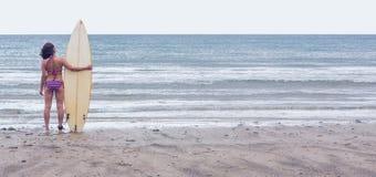 Kalme vrouw in bikini met surfplank op strand Royalty-vrije Stock Afbeelding