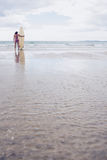 Kalme vrouw in bikini met surfplank op strand Stock Afbeeldingen