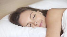 Kalme vrouwenslaap goed in comfortabel bed op zacht hoofdkussen stock video