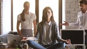 Kalme vrouwenwerknemer die in bureau mediteren die boze lastige collega's negeren stock videobeelden