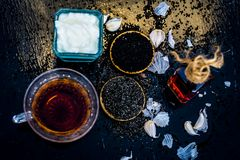 Kalonji with yogurt,garlic cloves,black tea and powder of roman coriander. Close up of kalonji with curd or yogurt on wooden surface with black tea and its Royalty Free Stock Image