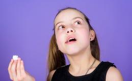 Kalori och att banta hungrig unge Of?rb?tterlig gottegris Flickan som ler framsidan, rymmer söta marshmallower i hand violetta royaltyfri foto