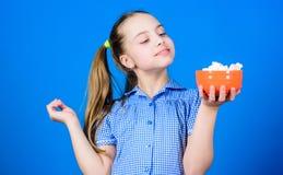 Kaloria i dieta Dziewczyny twarzy chwyta pucharu cukierk?w u?miechni?ci marshmallows w r?ki b??kita tle Dzieciak dziewczyna z d?u fotografia stock