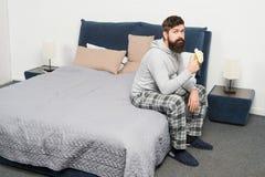 Kalorienimbiß Gesichtspyjamas des bärtigen Hippies des Mannes schläfrige, die Schlafzimmerinnenraum aufwachen Gesunder Lebensstil lizenzfreie stockbilder