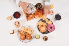 Kalorihamburgare med franska småfiskar, folk som äter på kafétabellen, sjuklig lunch royaltyfri fotografi