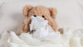 Kalt, Kamin oder Allergie Netter Teddybär im Bett, bedeckt mit einer warmen Decke, ein Gewebe halten stockfotos