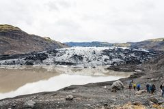 Tourists on hiking path to Solheimajokull glacier. KALTA GEOPARK, ICELAND - SEPTEMBER 9, 2017: tourists on hiking path to Solheimajokull glacier South glacial Royalty Free Stock Images