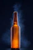 Kalte Bierflasche mit Tropfen auf Schwarzem Lizenzfreies Stockfoto