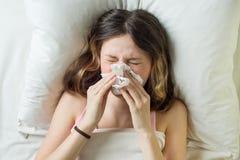 Kalte Grippe-Saison, laufende Nase Krankes Mädchen auf Bett niesend im Taschentuch im Schlafzimmer Lizenzfreie Stockbilder