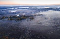 Kalte Herbstmorgenlandschaft mit Natur und Straße Luftbrummenfoto Nebel am Sonnenaufgang stockfotos