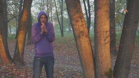 Kalte und Erwärmungshände des Gefühls des gutaussehenden Mannes, Mann friert im Herbstpark ein kalt stock footage