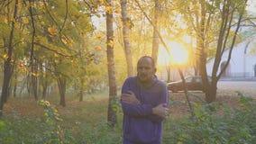 Kalte und Erwärmungshände des Gefühls des gutaussehenden Mannes, Mann friert im Herbstpark ein kalt stock video