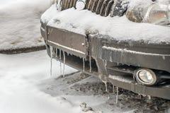 Kalter gefrorener Autostoßdämpfer in der Wintersaison in den Eiszapfen und im Schmutz Stockfotos