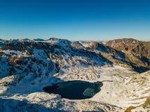 Kalter gefrorener Hochlandsee unter schneebedeckten Bergen, Arkhyz, Kaukasus, Russland stockbilder