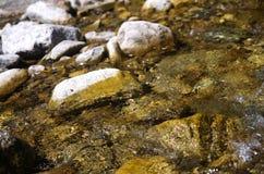 Kalter sauberer moutain Fluss, der auf den Steinen hetzt Stockfotografie