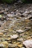 Kalter sauberer moutain Fluss, der auf den Steinen hetzt Lizenzfreie Stockfotos