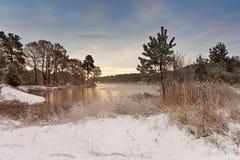 Kalter schneebedeckter Morgen auf dem See Spätherbst Jagd Bäume auf Seeufer stockfotos