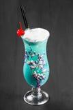 Kaltes alkoholisches blaues Cocktail, verziert mit Beeren und Blumen im Glas auf schwarzem hölzernem Hintergrund Lizenzfreie Stockfotografie