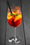 Kaltes alkoholisches Cocktail mit Kolabaum, Eis, Minze und Orange im Weinglas auf hölzernem Hintergrund Lizenzfreies Stockfoto