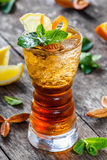 Kaltes alkoholisches Cocktail mit Kolabaum, Eis, Minze und Zitrone im Glas auf hölzernem Hintergrund Sommergetränke Lizenzfreies Stockbild