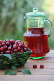 Kaltes Auffrischungsgetränk von den Kirschen in einem Pitcher und in reifen Beeren im Korb im Garten Stockbild