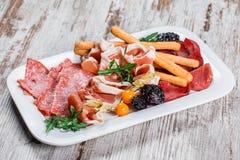 Kaltes Fleisch der Antipastoservierplatte mit grissini Brotst?cken, Prosciutto, Scheiben Schinken, Trockenfleisch vom Rind, Salam stockfotografie