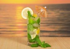 Kaltes Getränk mit Zitronenscheibe gegen den Seesonnenuntergang Lizenzfreie Stockfotografie