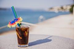 Kaltes Glas des Malibu-Kolabaumstands auf Tabelle nahe dem Meer stockbild