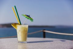 Kaltes Glas von Pina Colada-Stand auf Tabelle nahe dem Meer stockfoto