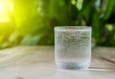 Kaltes Glaswasser auf Bretterboden Stockfotografie