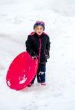 Kaltes Kind im Schnee mit Schlitten Lizenzfreies Stockbild
