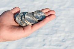 Kaltes Münzgeld - Silbermünzen in einer Hand des jungen Mannes Stockfoto