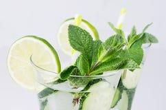 Kaltes natürliches Auffrischungscocktail mit Scheiben Gurke, Kalk, Minze, Eis, Stroh auf weißer hölzerner Planke, Nahaufnahme Lizenzfreies Stockbild