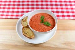 Kaltes Tomatensuppe gazpacho mit Basilikum und geschnittenes Brot in einer weißen Schüssel Lizenzfreies Stockfoto