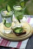 Kaltes Trinkwasser in einem Glas mit einer Gurke auf einem hölzernen Brett Stockbilder