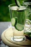 Kaltes Trinkwasser in einem Glas mit einer Gurke auf einem hölzernen Brett Stockfotos