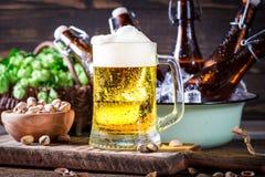 Kaltes und frisches selbst gemachtes Bier mit Pistazien Stockbild