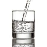 Kaltes Wasser gießt Wasser zum Glas auf Weiß Lizenzfreie Stockfotos