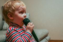 A little boy with microphone at karaoke party. royalty free stock images