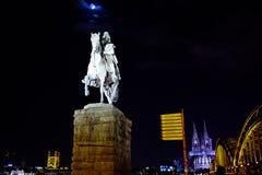 Kalvarienberg-Skulptur mit Köln-Kathedrale und hohenzollern Brücke Stockfotografie