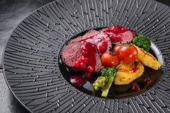 Kalvkött av medelstek med tranbärsås arkivbilder