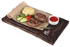 Kalvköttkotletter med mosade potatisar på portion pläterar rött mörker - royaltyfri fotografi