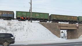 Kamaevo, Russia, 15 december 2016, train and workers at railroad at snow-covered winter village at sunny day. Wide angle stock footage