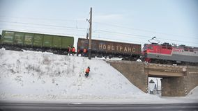 Kamaevo, Russia, 15 december 2016, workers at railroad at at snow-covered winter village at sunny day. Kamaevo, Russia, 15 december 2016, workers at railroad at stock footage