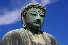 Kamakura Buddha. Head and shoulders of giant bronze Buddha statue in Japan, against a blue sky Stock Images