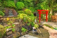 Benten-kutsu cave entrance. Kamakura, Japan - April 23, 2017: Japanese bamboo fountain in Hase-Dera garden or Hase-kannon and Torii gate or Shinto gate in front Stock Photos
