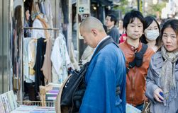 Japanese young priest buy something at Kamakura streets. KAMAKURA, JAPAN - MARCH 23,2014: Japanese young priest buy something at Kamakura streets royalty free stock photo