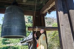 Monk and ancient temple bell in the Zen Buddhist Temple at Kamakura, Japan. KAMAKURA, JAPAN - MARCH 23,2014: Monk and ancient temple bell in the Zen Buddhist stock images